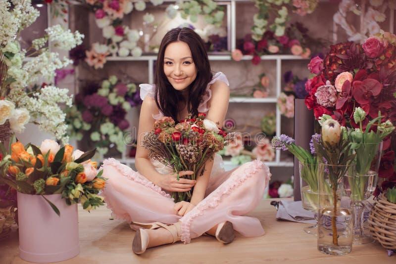 Florista asiático bonito da mulher no vestido cor-de-rosa com o ramalhete das flores nas mãos na loja de flor imagem de stock royalty free