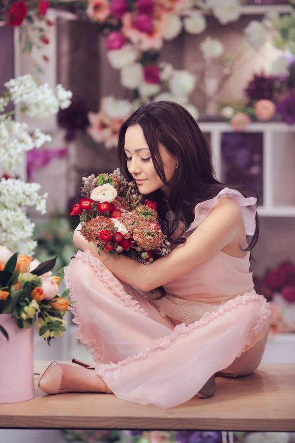 Florista asiático bonito da mulher no vestido cor-de-rosa com o ramalhete das flores nas mãos na loja de flor fotos de stock royalty free