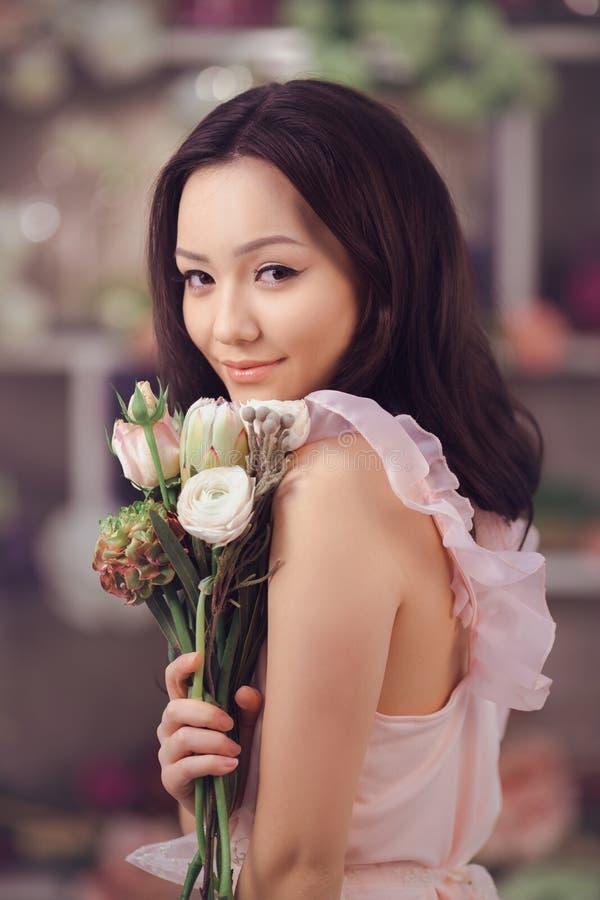 Florista asiático hermoso de la mujer en vestido rosado con el ramo de flores en manos en tienda de flor fotos de archivo