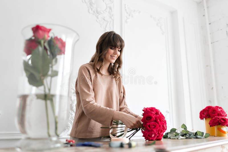 Florista bonito de sorriso da jovem mulher que arranja plantas no florista povos, negócio, venda e conceito floristry foto de stock