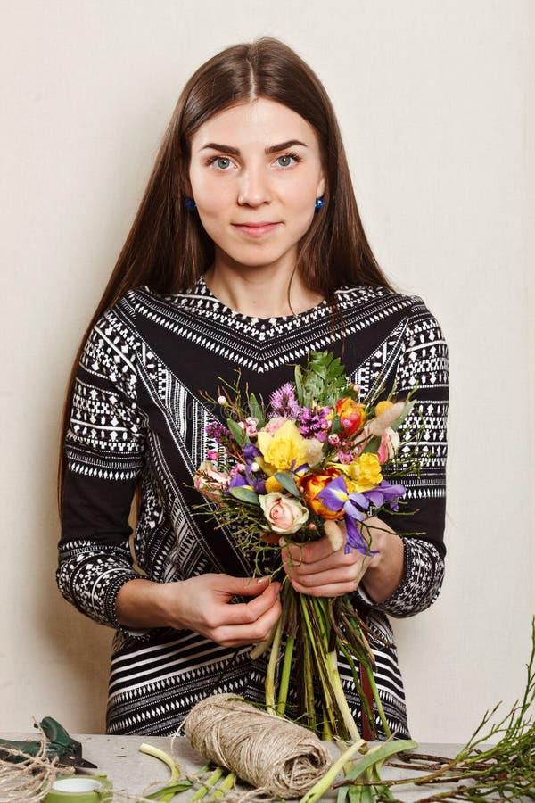 Florista bonito que faz o ramalhete das flores da mola foto de stock royalty free