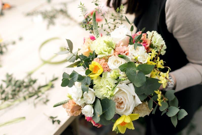 Florista da oficina, fazendo ramalhetes e arranjos de flor Mulher que recolhe um ramalhete das flores Foco macio fotos de stock royalty free
