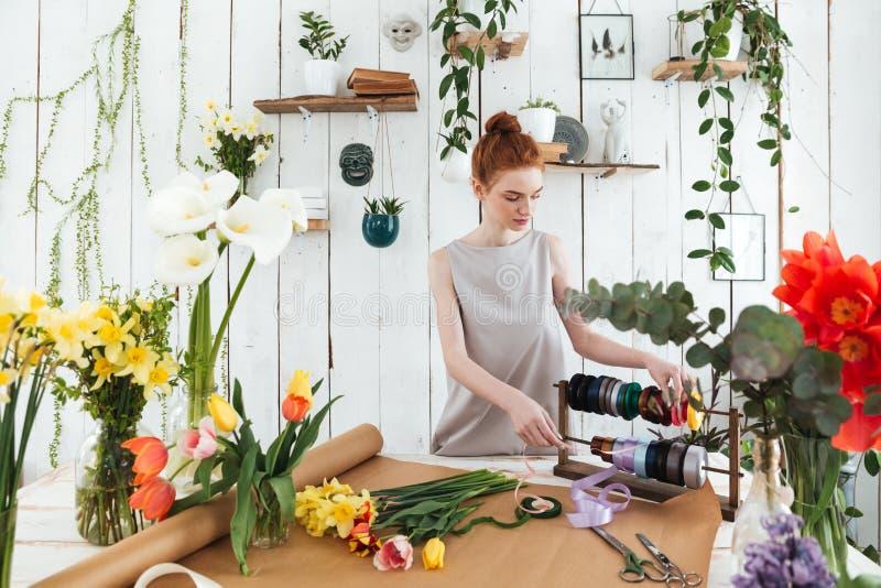Florista de la mujer joven que hace el ramo con las flores y las cintas imágenes de archivo libres de regalías