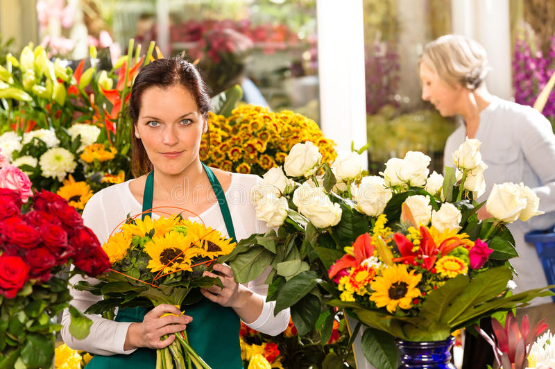 Florista de la mujer que vende la floristería del ramo de los girasoles imagen de archivo libre de regalías