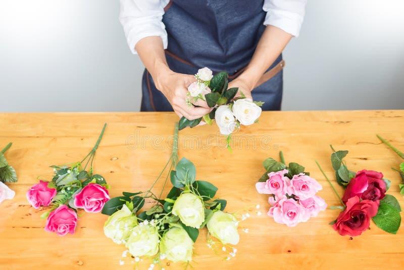 Florista de sexo femenino en el trabajo usando el arreglo del chaleco artificial hermoso de fabricación del ramo en la floristerí imágenes de archivo libres de regalías