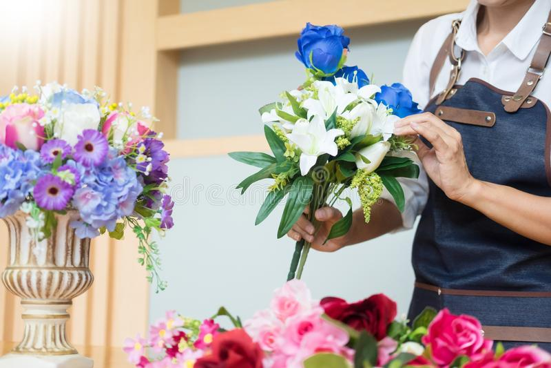 Florista de sexo femenino en el trabajo usando el arreglo del chaleco artificial hermoso de fabricación del ramo en la floristerí foto de archivo libre de regalías