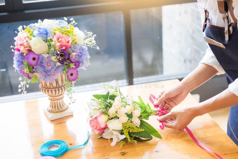 Florista de sexo femenino en el trabajo usando el arreglo del chaleco artificial hermoso de fabricación del ramo en la floristerí imagenes de archivo