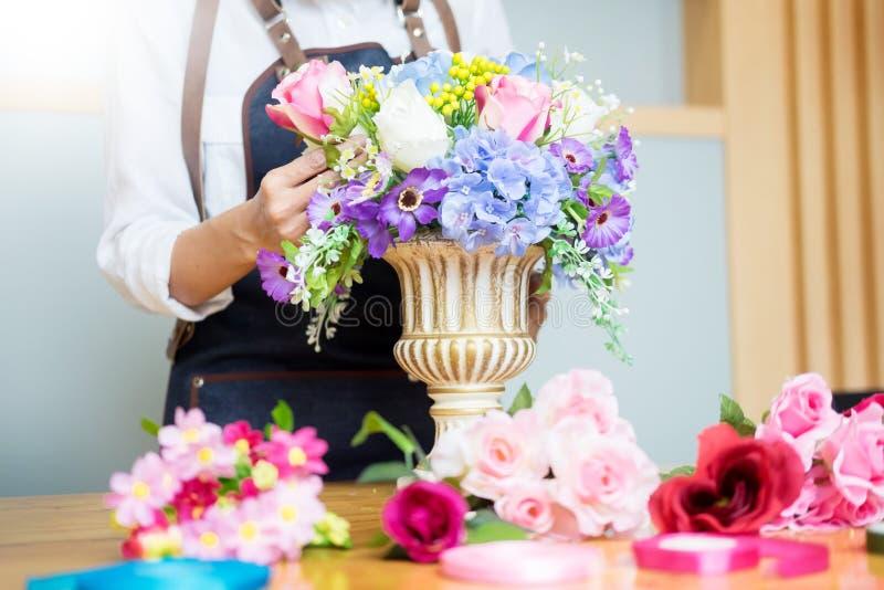 Florista de sexo femenino en el trabajo usando el arreglo del chaleco artificial hermoso de fabricación del ramo en la floristerí foto de archivo