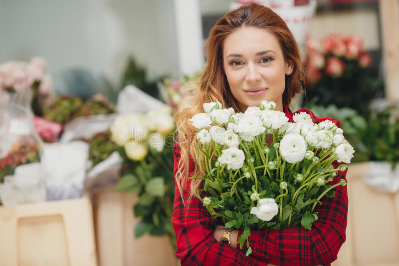 Florista de sexo femenino hermoso en floristería fotos de archivo