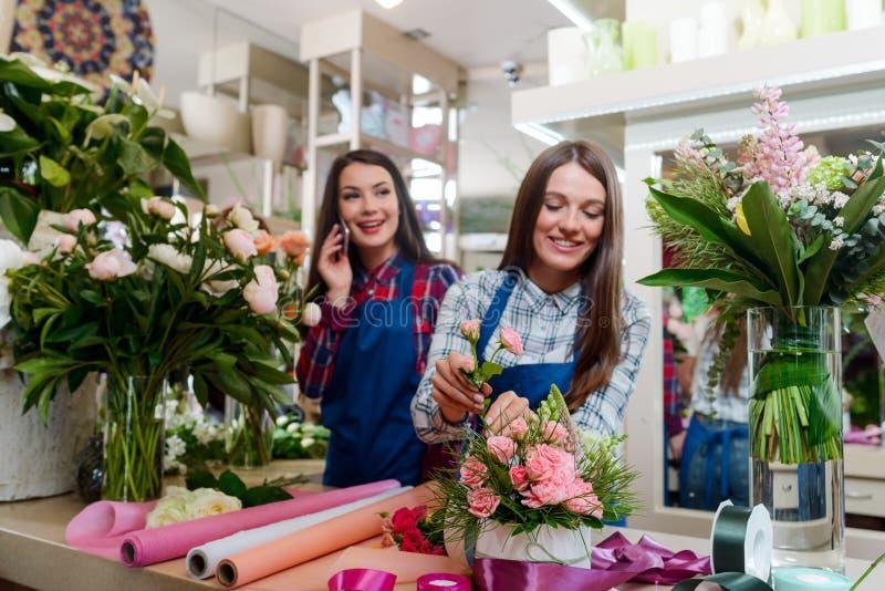 Florista de sexo femenino que arregla un ramo imagenes de archivo