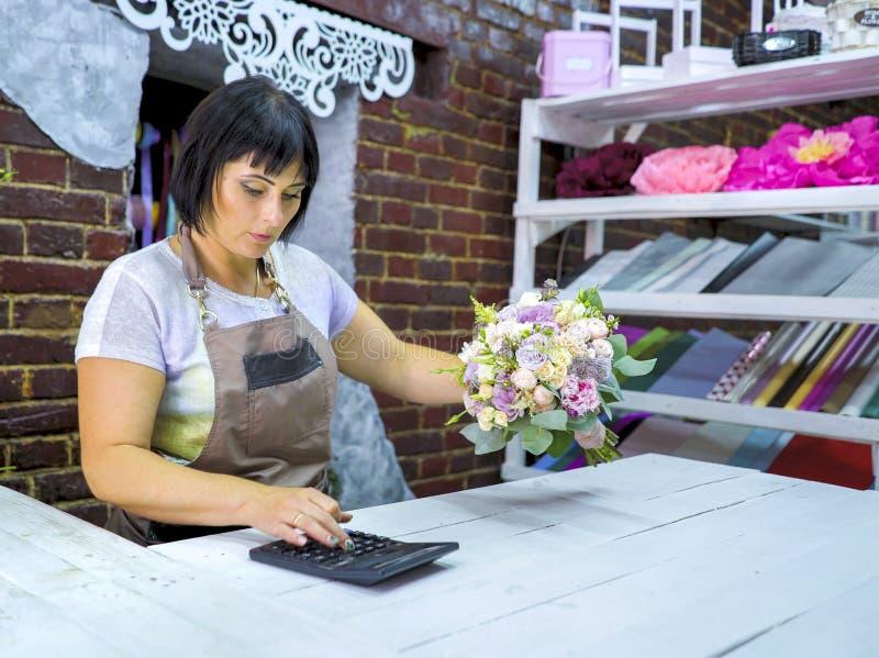 Florista de sexo femenino que cuenta el coste del ramo con la calculadora en una floristería imagen de archivo libre de regalías
