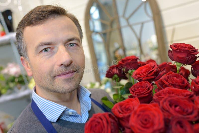 Florista de sexo masculino del retrato que sostiene rosas imagenes de archivo