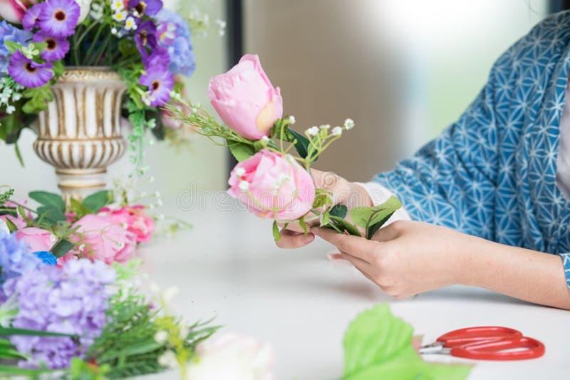 Florista do propriet?rio empresarial das jovens mulheres que faz ou que arranja a veste das flores artificiais em seus loja, of?c foto de stock royalty free
