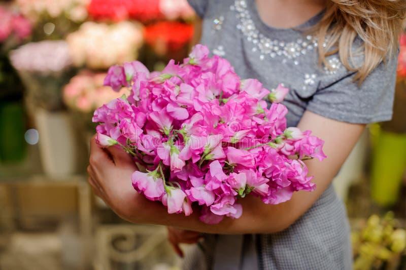 Florista em um vestido cinzento que guarda um ramalhete cor-de-rosa macio bonito das flores imagem de stock royalty free