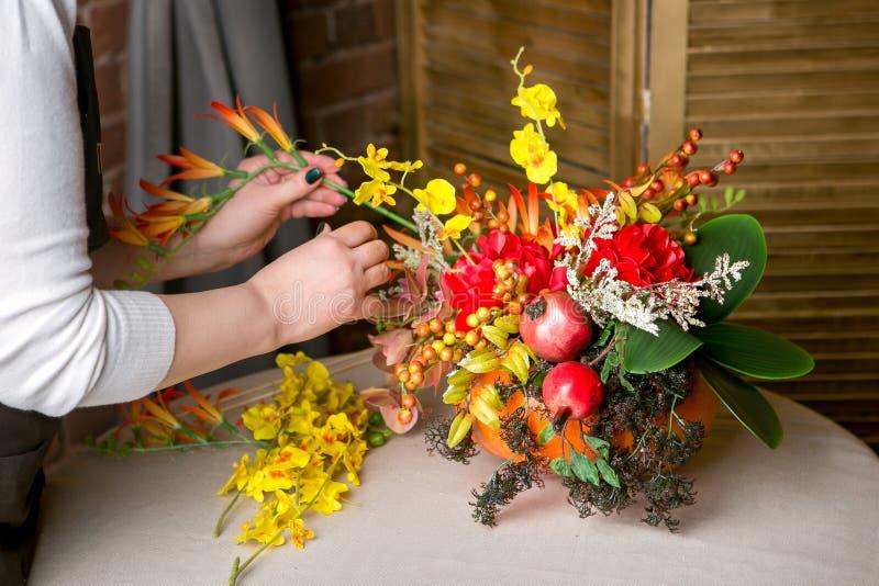 Florista en el trabajo: Cómo hacer una pieza central de la acción de gracias con la calabaza y el ramo grandes de flores Paso a p fotografía de archivo