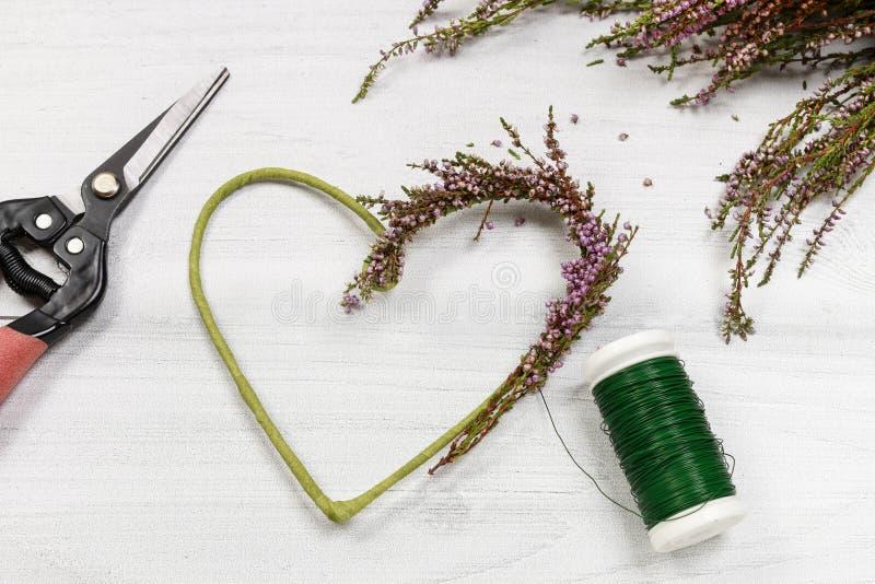 Florista en el trabajo: pasos de hacer la guirnalda de la puerta de Erica del brezo adentro foto de archivo