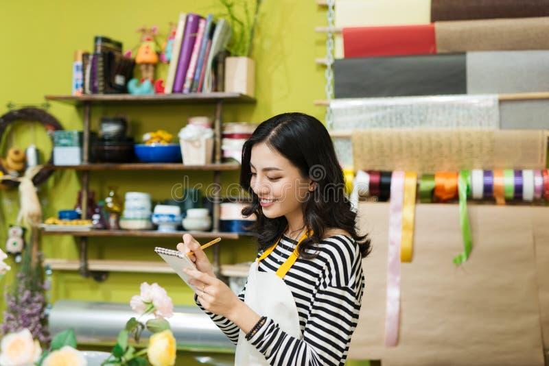 Florista fêmea asiático de sorriso que faz anotações no contador do florista imagem de stock