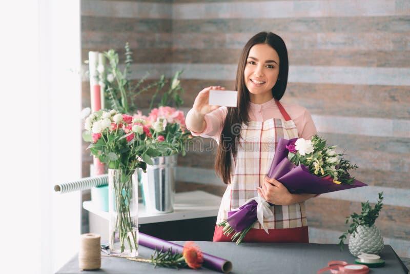 Florista fêmea no trabalho: morena consideravelmente nova que faz a forma o ramalhete moderno de flores diferentes Trabalho das m foto de stock royalty free