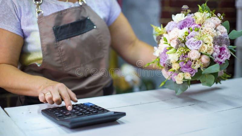 Florista fêmea que conta o custo do ramalhete com calculadora em um florista fotografia de stock