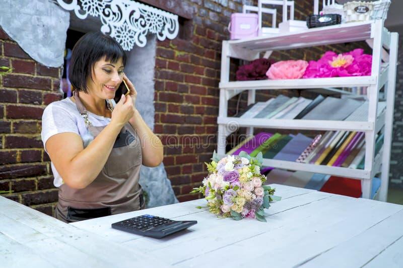 Florista fêmea que fala no telefone que discute o custo do ramalhete com o cliente em um florista imagens de stock
