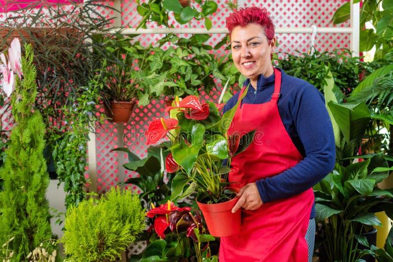 Florista feliz de la mujer, tomando medidas, y sonriendo en la cámara Dueño de floristería de la pequeña empresa fotografía de archivo libre de regalías