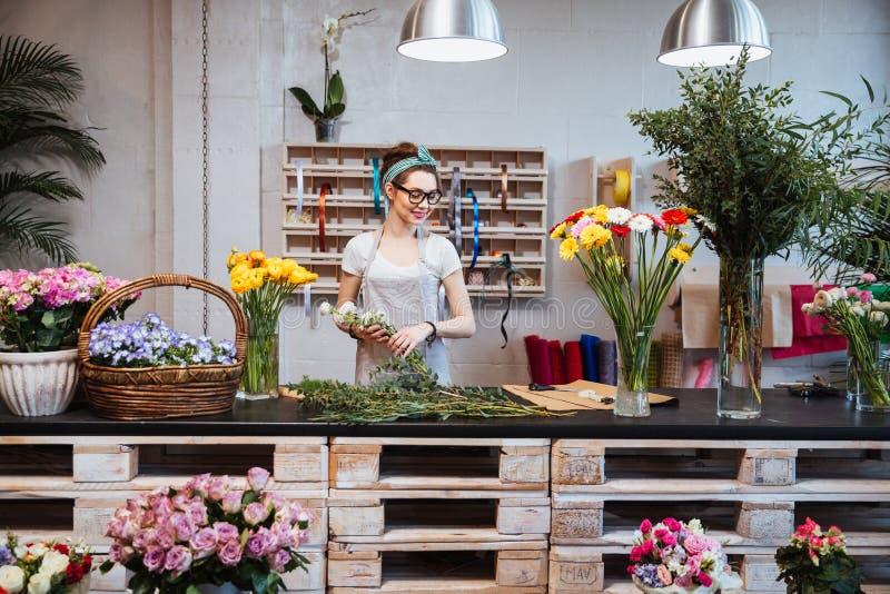 Florista hermoso alegre de la mujer que sonríe y que trabaja en floristería fotos de archivo