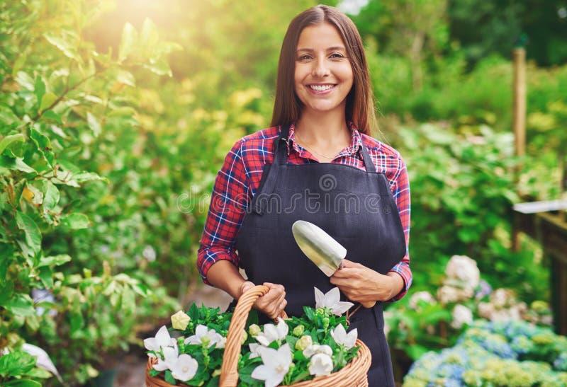 Florista joven feliz que trabaja en un invernadero imagenes de archivo