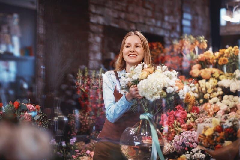 Florista joven sonriente en la tienda imagenes de archivo