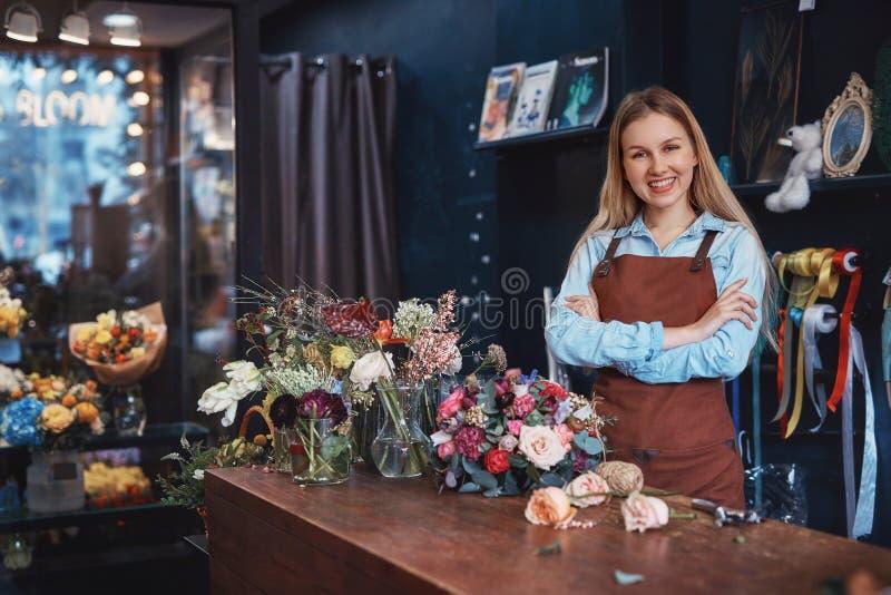 Florista joven sonriente en un delantal foto de archivo