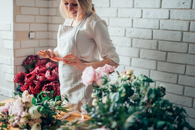 Florista que fotografía el ramo en el teléfono Fotografía de Mibile fotos de archivo