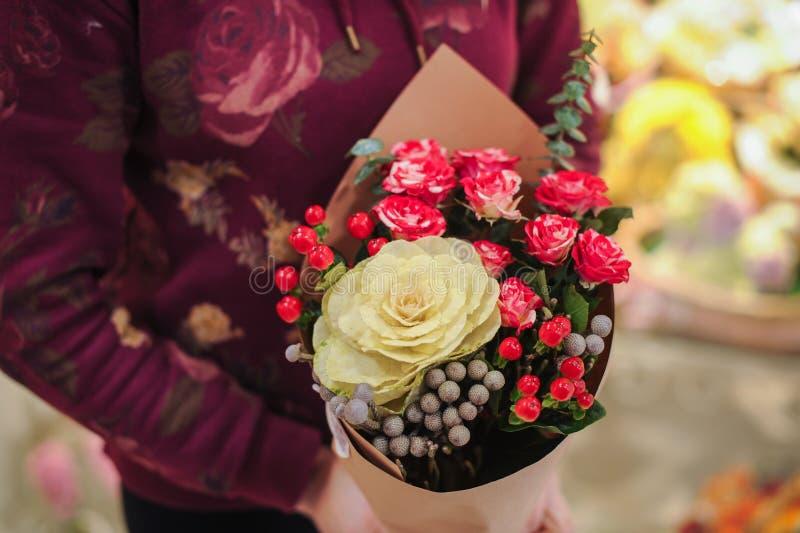 Florista que guarda as mãos coloridas do assistente de loja das flores do ramalhete fotografia de stock royalty free