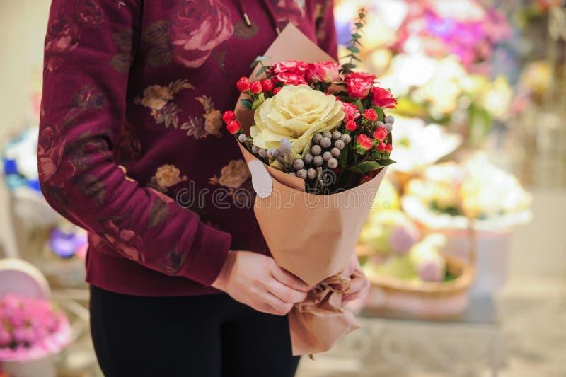 Florista que guarda as mãos coloridas do assistente de loja das flores do ramalhete imagem de stock royalty free