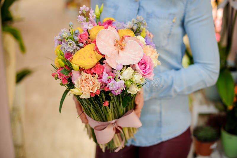 Florista que guarda um ramalhete colorido bonito das flores com uma curva bonito imagens de stock