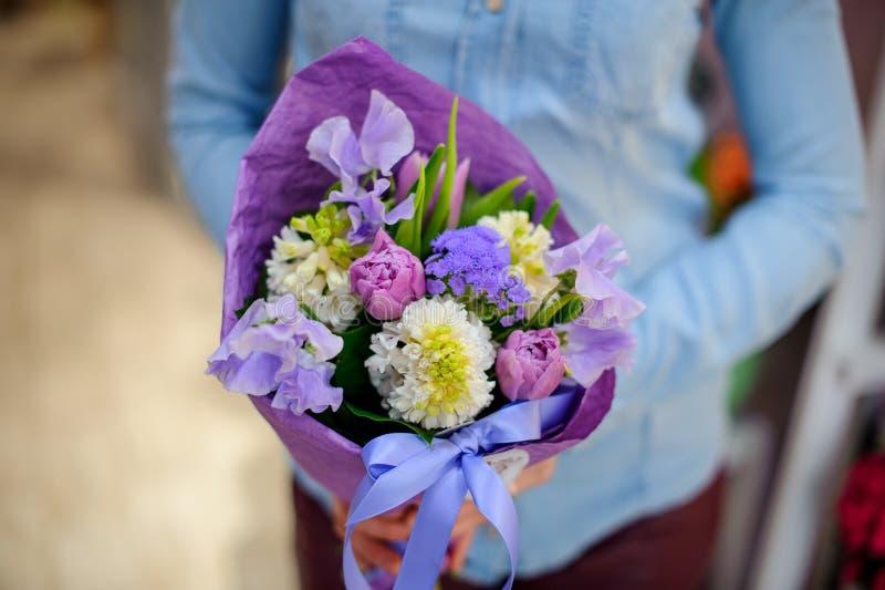 Florista que guarda um ramalhete roxo bonito e bonito das flores imagens de stock royalty free