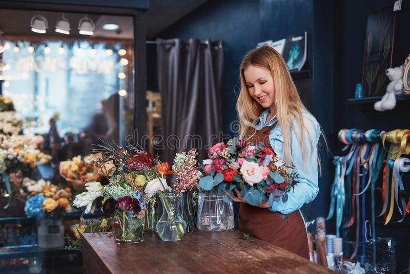 Florista sonriente con el ramo dentro foto de archivo