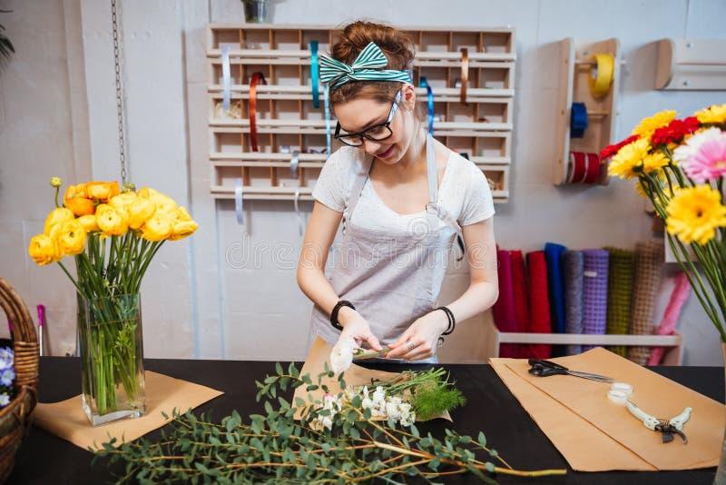 Florista sonriente de la mujer que coloca y que hace el ramo en floristería imagen de archivo libre de regalías