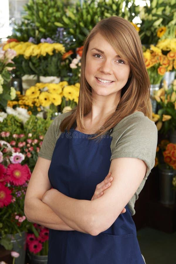 Florista Standing In Shop por la exhibición colorida de flores fotografía de archivo libre de regalías