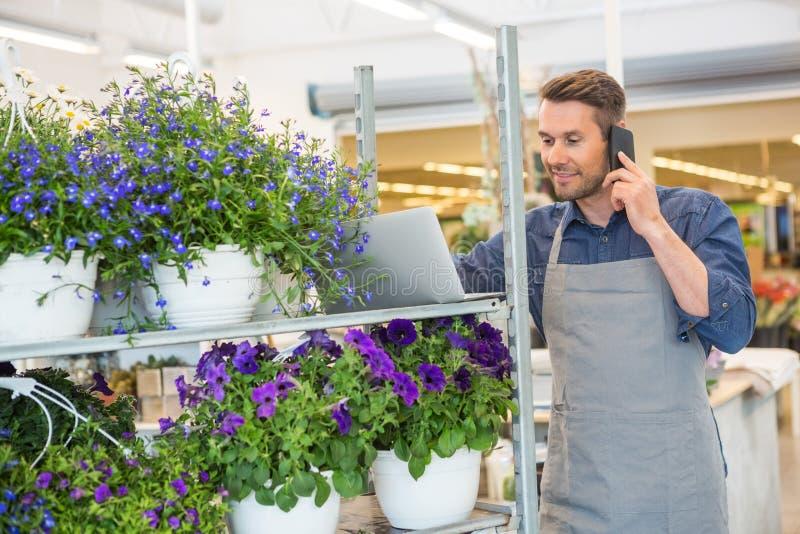 Florista Using Mobile Phone y ordenador portátil en tienda foto de archivo libre de regalías