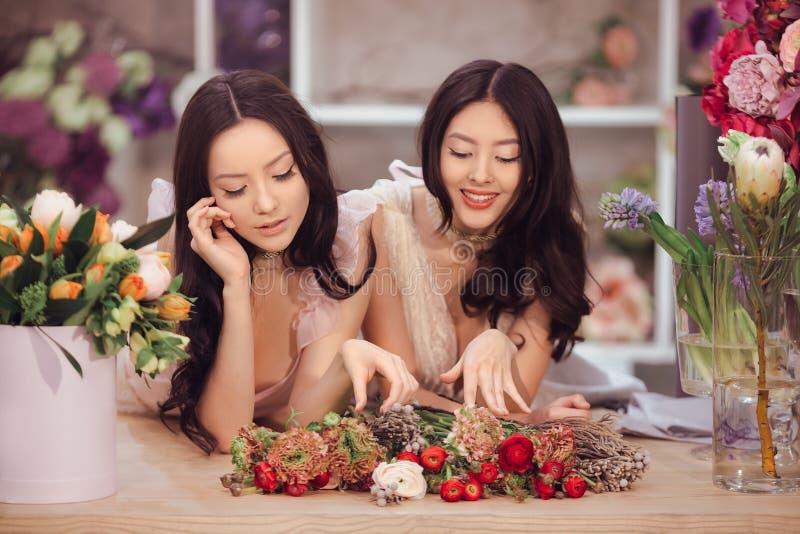 Floristas asiáticos bonitos das mulheres com o ramalhete das flores na loja de flor imagens de stock royalty free