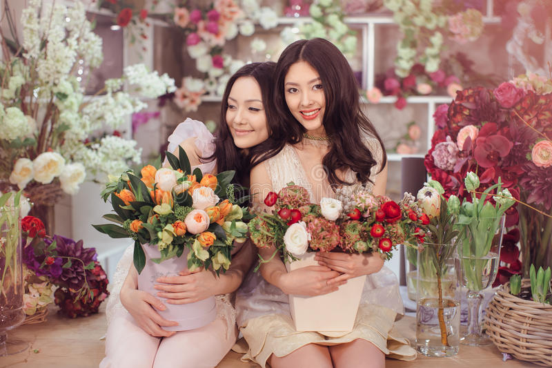 Floristas asiáticos bonitos das mulheres com o ramalhete das flores na loja de flor imagem de stock royalty free