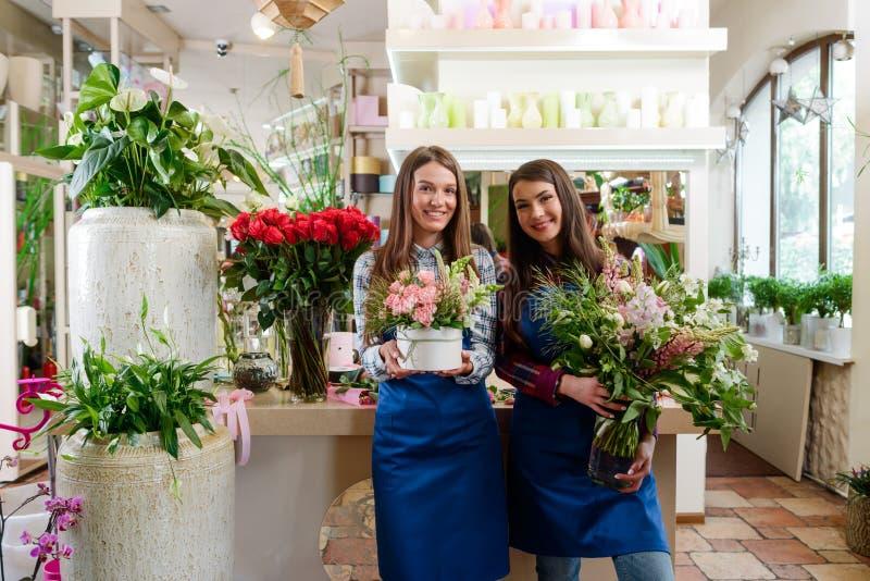 Floristas fêmeas que levantam com ramalhetes foto de stock royalty free