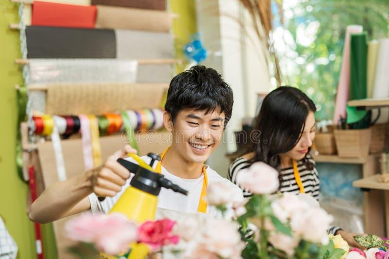 Floristas masculinos e fêmeas com os ramalhetes bonitos no florista foto de stock royalty free