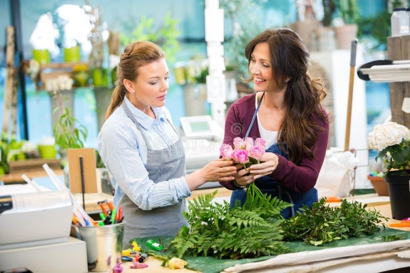 Floristas que fazem o ramalhete das rosas na loja imagens de stock royalty free