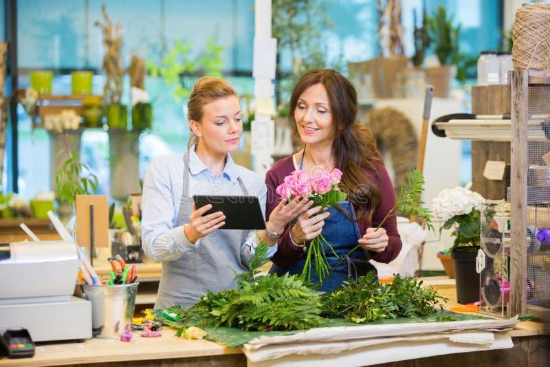 Floristas que usam a tabuleta de Digitas ao fazer o ramalhete foto de stock royalty free