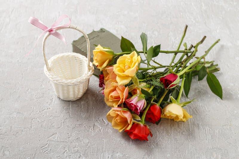 Floristenarbeitsplatz: wie man Blumengesteck mit Rosen herein trifft lizenzfreie stockbilder