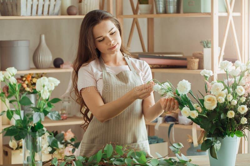 Floristenbesetzung der jungen Frau, die mit Blumen arbeitet lizenzfreies stockbild