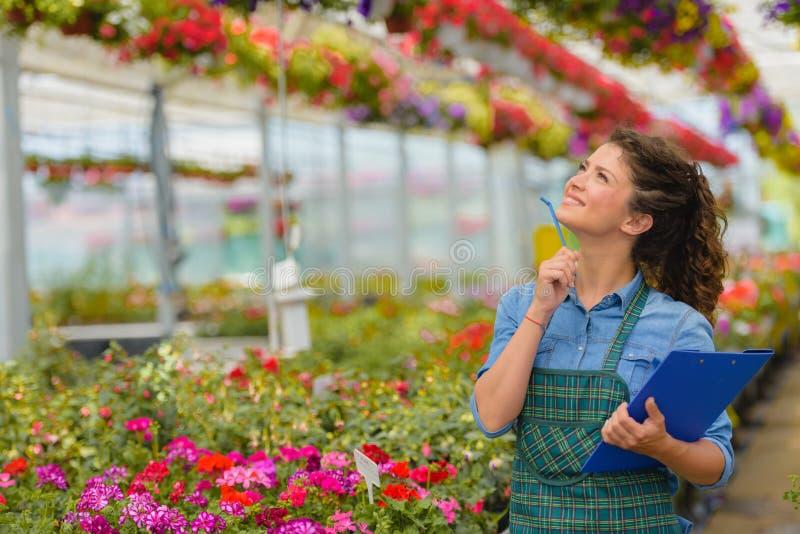 Floristenfrau, die mit Blumen in einem Gewächshaus arbeitet lizenzfreies stockbild
