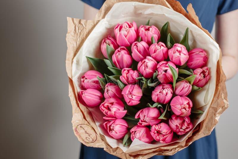 Floristenmädchen mit Pfingstrosenblumen oder rosa Blumenblumenstrauß der jungen Frau der Tulpen für Geburtstagsmuttertag stockbilder