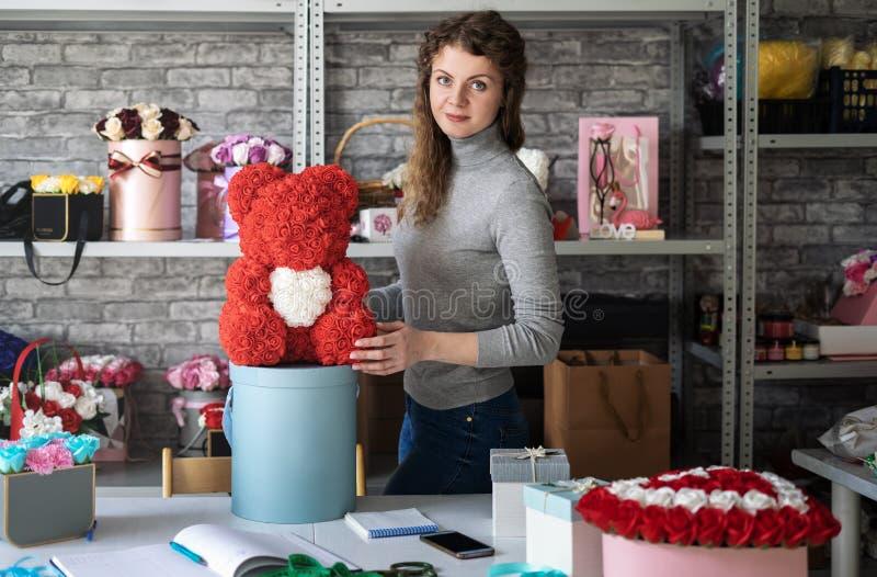 Floristería: La muchacha del florista muestra un oso de peluche de pequeñas rosas rojas Alrededor del taller y de mucho diverso f imagenes de archivo