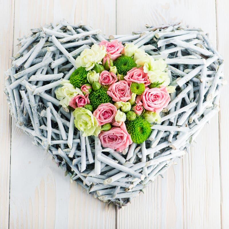 Floristic sammansättning av hjärtan med nya blommor på en woode royaltyfri bild